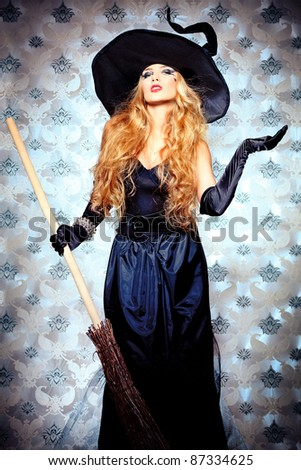 Charming halloween witch with broom over vintage background. - stock photo