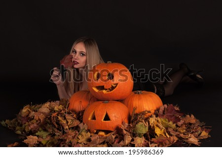 Charming halloween witch with funny pumpkins and leaves over black background