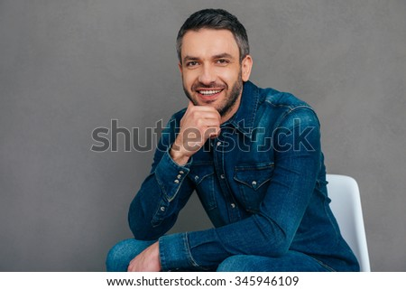 Charming handsome. Confident mature man in jeans shirt holding hand on chin and smiling while sitting on the chair against grey background - stock photo