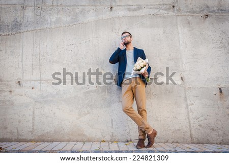 Charming handsome. Full length of handsome young man in smart jacket holding bouquet of roses and talking on the mobile phone while leaning at the concrete wall outdoors - stock photo