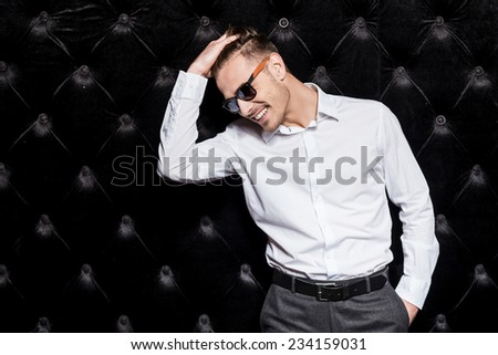 Charming handsome. Handsome young man in white shirt holding hand in hair and smiling while standing against black background  - stock photo