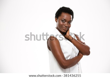 Charming happy african american young woman standing with hands folded over white background - stock photo