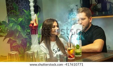 charming happy couple smokes shisha and drink cocktails at the bar - stock photo