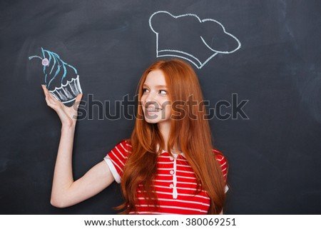 Charming happy redhead young woman in drawn chef hat holding drawing cupcake over blackboard background - stock photo