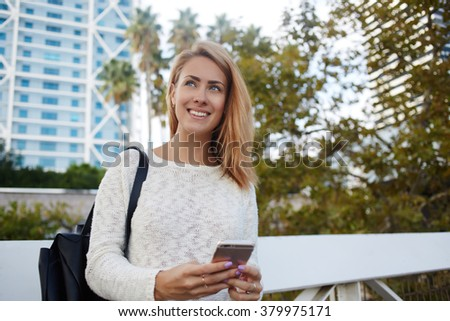 Charming happy woman holding cell telephone and looking away while standing in the fresh air in warm spring day, smiling hipster girl using mobile smart phone while waiting for her friends outdoors