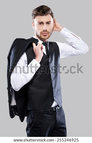 Charming heartbreaker. Confident young and handsome man in formalwear carrying jacket and adjusting his hair while standing against grey background - stock photo