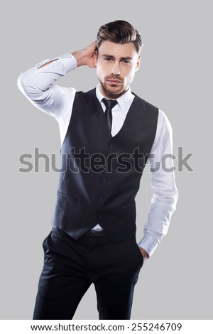 Charming heartbreaker. Confident young and handsome man in formalwear holding hand in hair and looking at camera while standing against grey background - stock photo