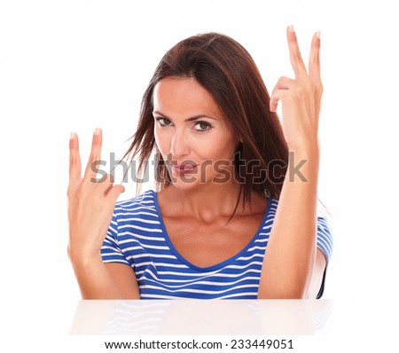 Charming hispanic lady with fingers up gesturing winning while looking at camera in white background - stock photo