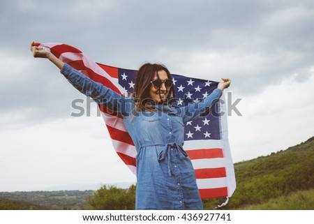 Charming independent american girl on cloudy day in the summertime, in vivid green meadow, waving an american flag - stock photo