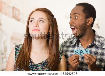 Charming interracial couple holding up small letters spelling the say while interacting happily, blurry studio background - stock photo