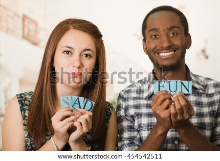 Charming interracial couple holding up small letters spelling the words sad and fun, both with facial expressions matching their word, blurry studio background - stock photo
