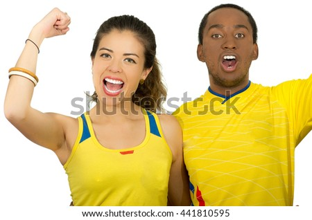 Charming interracial couple wearing yellow football shirts cheering joyfully to camera, white studio background - stock photo