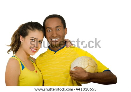 Charming interracial couple wearing yellow football shirts, hugging friendly while posing for camera holding ball, white studio background - stock photo