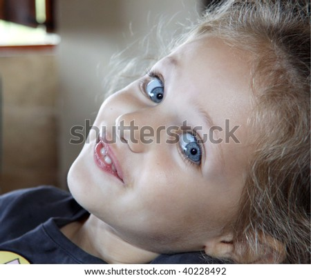 charming kid portrait with blue eyes and a cheeky grin - stock photo