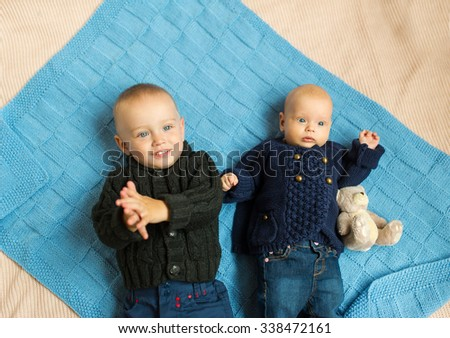charming kids lie on a blue cover - stock photo