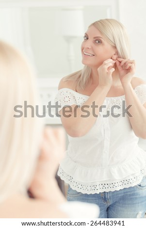Charming lady. Attractive smiling woman putting on earring looks at her reflection in the mirror - stock photo
