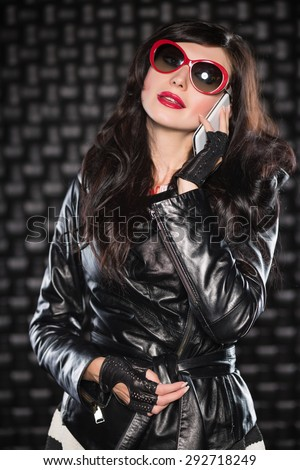 Charming lady in black leather jacket and red sunglasses talking on the phone - stock photo