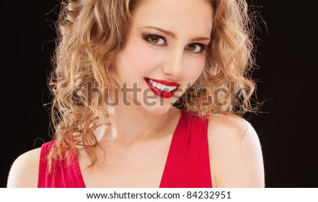 Charming lady in red evening dress, isolated on black background.