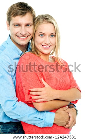 Charming lady posing with her hands crossed and her husband embracing from behind - stock photo