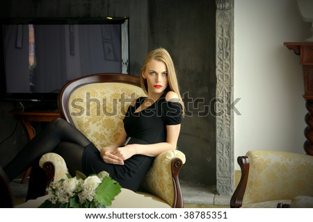 charming lady seated in a classical armchair - stock photo