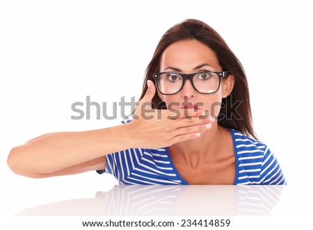 Charming lady with glasses looking surprised and feeling embarrassed while looking at camera front view in white background - stock photo