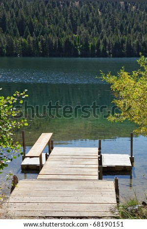 Charming lake in California. Wooden convenient dock for boats - stock photo