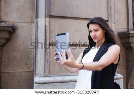 Charming latin woman making self portrait on her digital tablet camera while walking on the street in summer day, beautiful female posing while photographing herself for social network picture - stock photo