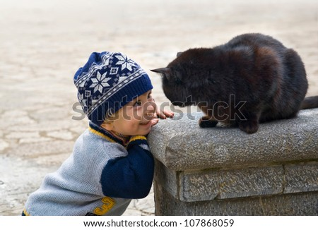 Charming little boy playing with black cat