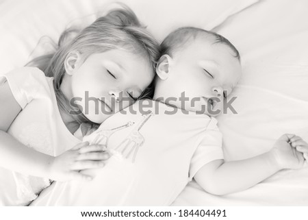 charming little brother and sister asleep embracing on white background ( black and a white ) - stock photo