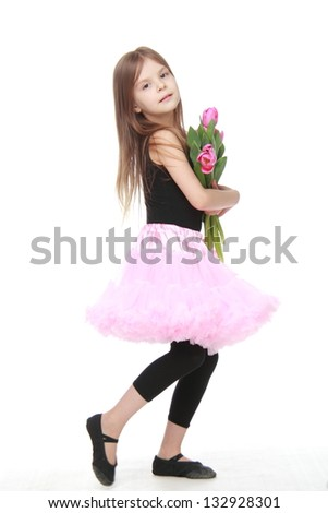 Charming little dancer with long blond hair holding a beautiful bouquet of pink tulips - stock photo