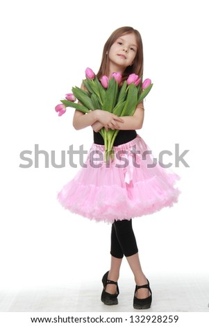 Charming little dancer with long blond hair holding a beautiful bouquet of pink tulips on Beauty and Fashion - stock photo