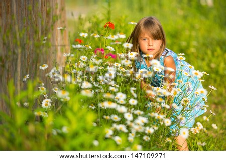 Charming little girl among yellow wildflowers - stock photo