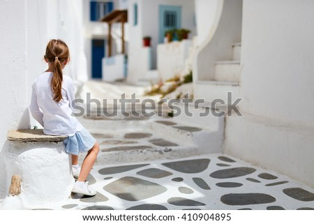 Charming little girl at typical greek traditional village with white houses and colorful doors on Mykonos Island, Greece, Europe - stock photo