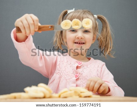 Charming little girl cutting a ripe banana on grey background - stock photo