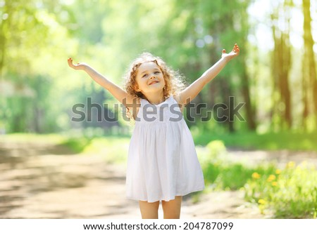 Charming little girl enjoying summer sunny day, raises his hands top, expression emotions, happy child walking in the park  - stock photo