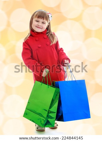 Charming little girl goes shopping with large multi-colored packages. - stock photo