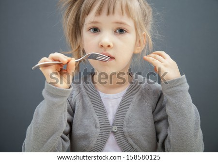 Charming little girl holding a fork, grey background - stock photo