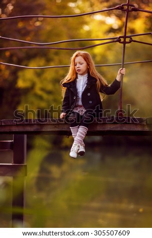 Charming little girl in a black coat in the fall on the bridge