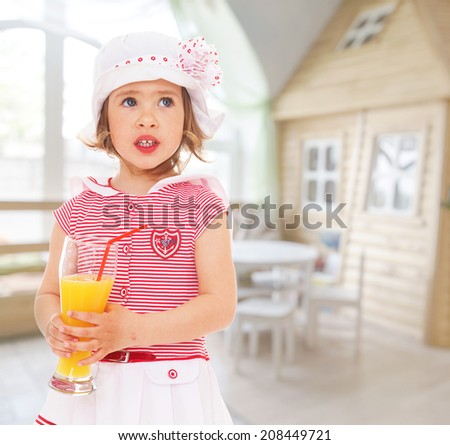 charming little girl in a hat with a glass of orange juice.kindergarten, the concept of childhood and joy, teens - stock photo