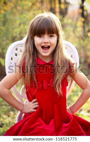 Charming little girl in a red dress sitting on a chair in the autumn forest - stock photo