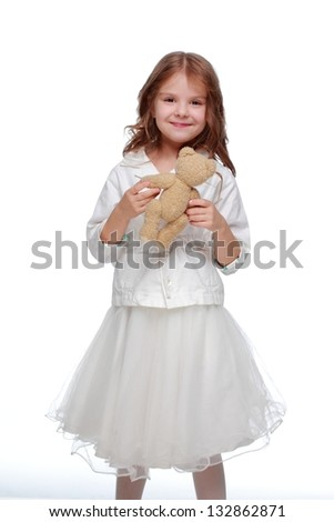 Charming little girl in beautiful white dress holding a soft teddy bear on a white background