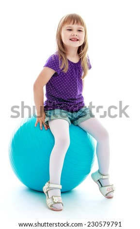 charming little girl in blue shorts playing with a big blue ball. Happy childhood, fashion, autumnal mood concept. Isolated on white background - stock photo
