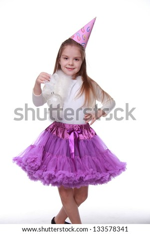 Charming little girl in holiday dress posing for the camera and smiling on white background