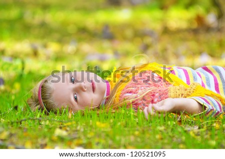 Charming little girl lies of the grass in the park