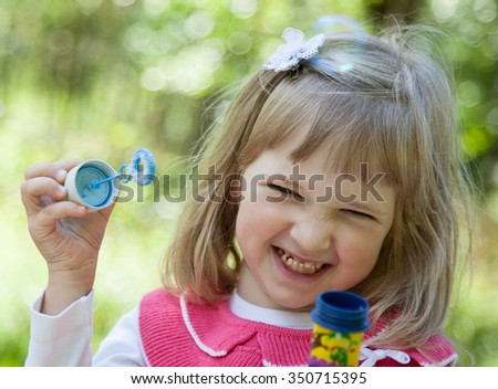Charming little girl making soap bubbles in a summer park - stock photo