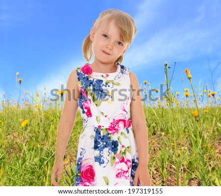 Charming little girl on summer meadow of tall flowers. - stock photo