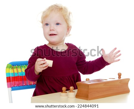 Charming little girl playing at the table, isolated on white background. - stock photo