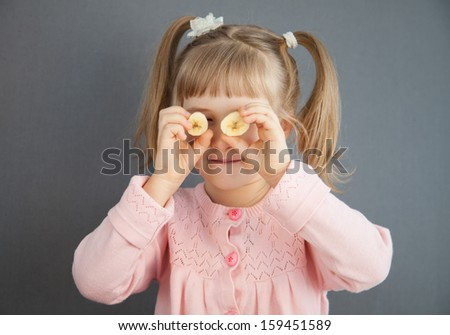 Charming little girl playing with pieces of a ripe banana, grey background - stock photo