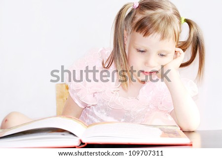 Charming little girl reading book - stock photo