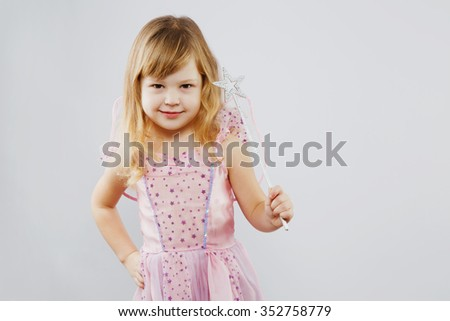 Charming little girl, with curly blond hair, wearing on pink dress and fairy wings on her back, posing with magic stick and looking at camera, on white background, in studio, waist up - stock photo